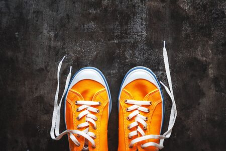 yellow-orange sneakers with untied laces on a dark concrete background. Copy space. View from above Stockfoto