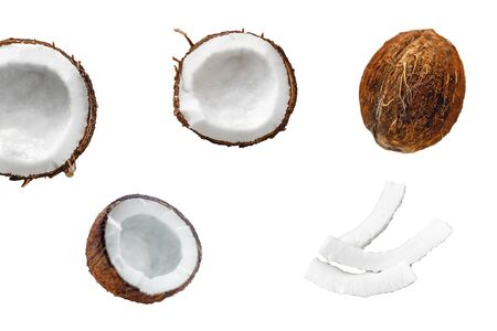 Whole coconut and cut into chunks and chips on a light white wooden background.