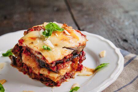 Tradicional Parmigiana di melanzane : aubergines au four - Italie, sicile cousine.,Aubergines au four avec fromage, tomates et épices sur une assiette blanche. Un plat d'aubergine est sur une table en bois Banque d'images