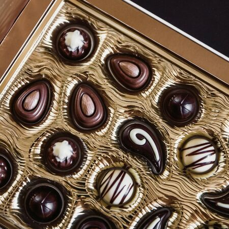 Chocolate candies of different shapes in a gold box, View from above. Background Stock Photo
