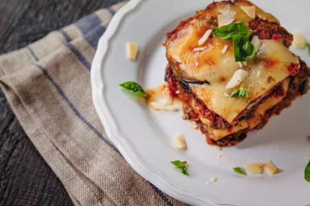 tradicional Parmigiana di melanzane: baked eggplant - italy, ,sicily cousine.Baked eggplant with cheese, tomatoes and spices on a white plate. A dish of eggplant is on a wooden table