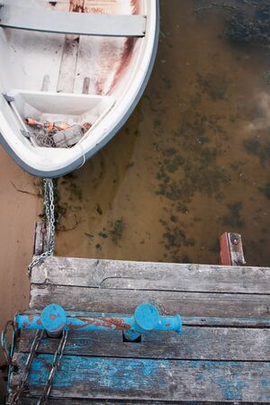 Old boat on an old wooden blue wharf on a river-lake. Top view, close up. Standard-Bild - 130757628