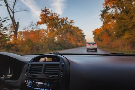 A man driving a car on an autumn yellow-orange road. Close-up of a hand. Standard-Bild - 130757685