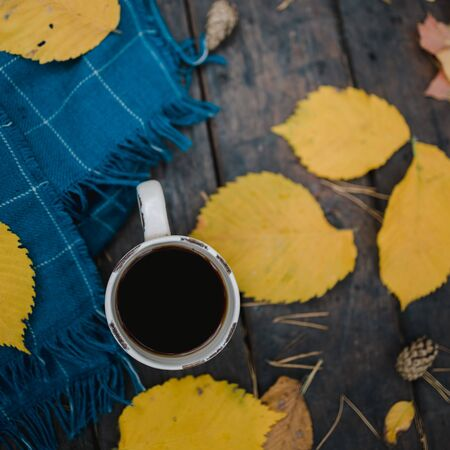 On a old wooden table in the autumn park is a cup of tea-coffee. A blue warm plaid scarf is scattered with yellow leaves and pine cones. Top view, blurred. Autumn warm dark mood, copy space. Stock fotó