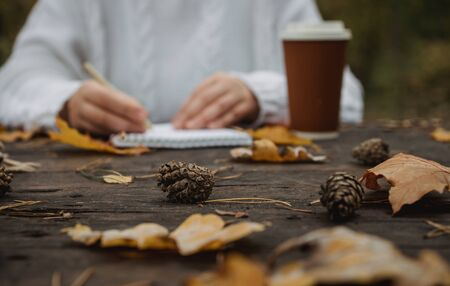 Human hands with a cup of coffee and scarf at wooden table with notebook and pen and autumn leaves. Human hands with a cup of coffee and scarf at wooden table. Stock Photo