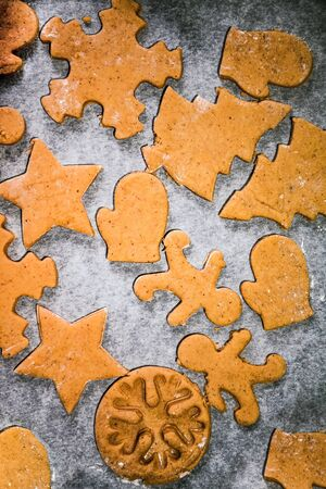 cut out gingerbread cookie in the form of a Christmas tree, star, little man, hearts from raw dough on parchment baking paper on a dark background. Top view. save space. Stockfoto