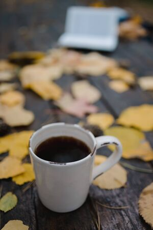 On a old wooden table in the autumn park is a cup with tea and coffee, scattered yellow leaves and pine cones. Top view, in blur. Autumn warm dark mood, soft focus Stock fotó