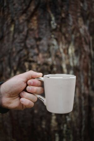 hand holds a cup of tea with coffee on the background of an old wooden trunk. Warm autumn atmosphere, soft focus