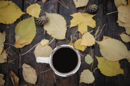 On a old wooden table in the autumn park is a cup with tea and coffee, scattered yellow leaves and pine cones. Top view, in blur. Autumn warm dark mood, soft focus Reklamní fotografie