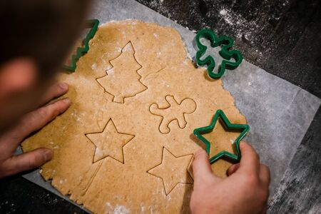 male hands cut out gingerbread cookie in the form of a snowflake, Christmas tree, a man from raw dough on parchment baking paper on a dark background. View from above. save space.