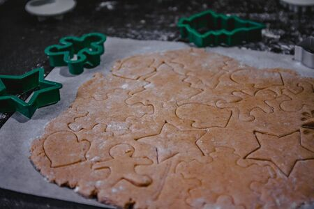 cut out gingerbread cookie in the form of a Christmas tree, star, little man, hearts from raw dough on parchment baking paper on a dark background. Top view. save space. Zdjęcie Seryjne