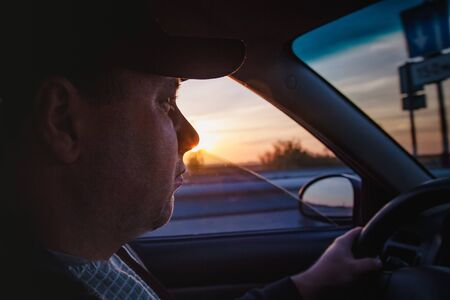 man driving a car at sunset-dawn, close-up, blur. Concept, road trips and travel, freedom of movement. Reklamní fotografie