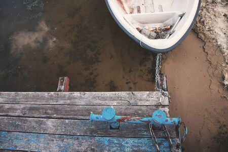 Old boat on an old wooden blue wharf on a river-lake. Top view, close up.