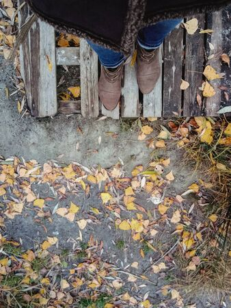 top view of female legs with brown boots on a background of yellow autumn leaves and a wooden platform. Copy space.