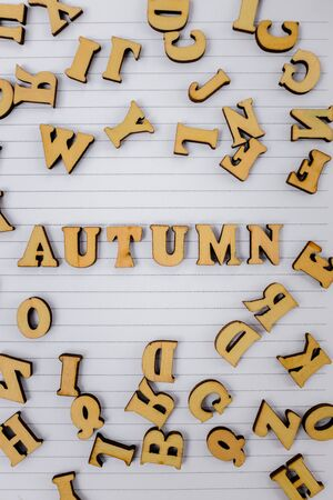 white notebook with scattered wooden letters and the phrase autumn, top view
