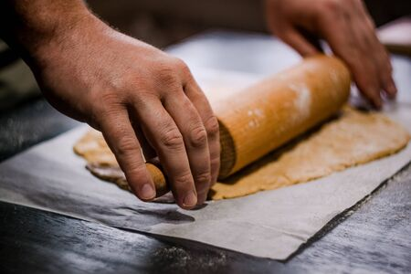 bakers hands roll ginger dough on a dark background. Close-up, soft focus. Side view, top view. Copy space