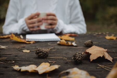 young woman in a white sweater sits at an old dark table in the park, holds a cup of tea with coffee and reads and writes on the background of yellow autumn leaves. Warm autumn atmosphere, soft focus. Copy space. Zdjęcie Seryjne