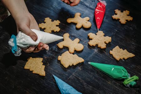 decorate Christmas gingerbread cookies using colored glaze on a dark wooden table, top view.