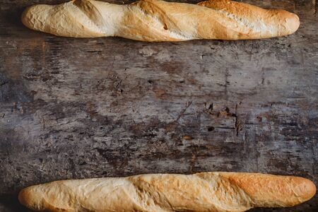 Fresh rosy baguettes on a dark wooden retro background. Top view, copy space.