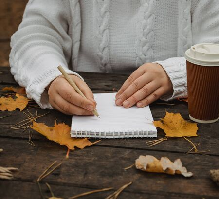 Human hands with a cup of coffee and scarf at wooden table with notebook and pen and autumn leaves. Human hands with a cup of coffee and scarf at wooden table. Zdjęcie Seryjne
