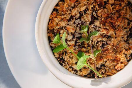 baked oat-blueberry crumble with mint in a white and blue plate on a rustic linen tablecloth. Save the space, top view. The concept of healthy proper nutrition for breakfast, vegetarianism