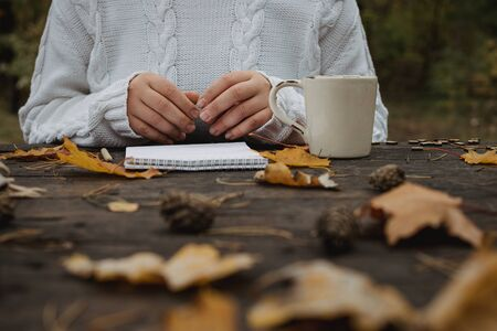young woman in a white sweater sits at an old dark table in the park, holds a cup of tea with coffee and reads and writes on the background of yellow autumn leaves. Warm autumn atmosphere, soft focus. Copy space. 版權商用圖片