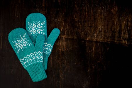 a pair of blue knitted mittens on a dark blue-green-brown wooden vintage background, copy space.