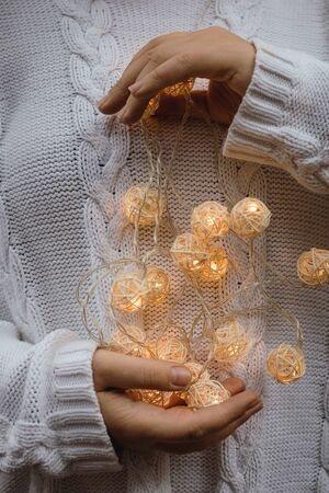lights in the palms. Female hands hold a garland with wicker round balls. Girl in a white sweater with Christmas lights in her hands, warm New Year mood, soft focus. 版權商用圖片