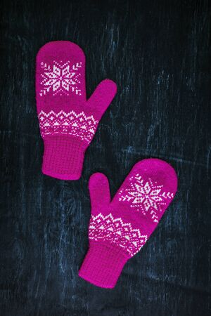 a pair of red-pink-lilac-magenta purple knitted mittens on a dark blue-green-brown wooden vintage background, copy space.