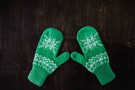 a pair of blue-green knitted mittens on a dark blue-green-brown wooden vintage background, copy space.