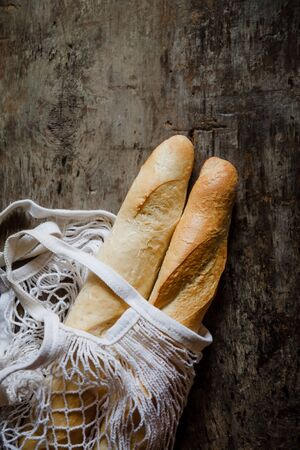 Fresh rosy baguettes in a string bag on a dark wooden retro background. Top view, copy space. 版權商用圖片