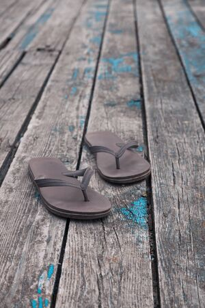 brown flip flops slippers on old wooden deck mooring background.
