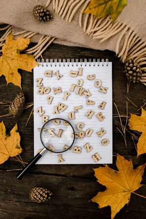 notebook with wooden letters and a magnifying glass on a dark background with a scarf, plaid, around autumn yellow leaves and pine cones. View from above. flat lay. Copy space