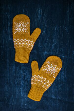 a pair of yellow orange knitted mittens on a dark blue-green-brown wooden vintage background, copy space. 版權商用圖片