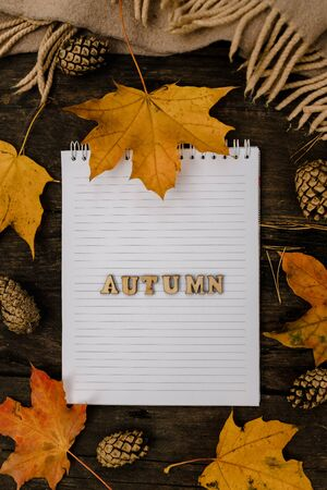 White blank notebook and pen with wooden letters the word autumn on a dark background with a scarf, plaid and a cup, autumn yellow leaves and pine cones around. View from above. flat lay, in blur. Copy space