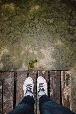 top view of female legs in white sneakers and jeans on the background of an old dirty autumn lake-river and a wooden platform. Copy space.