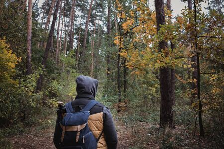 A young guy with a backpack in the hat, traveler, hipster standing in the woods, Hiking, Forest,Journey.