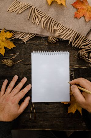 Human hands with a cup of coffee and scarf at wooden table with notebook and pen and autumn leaves. Human hands with a cup of coffee and scarf at wooden table
