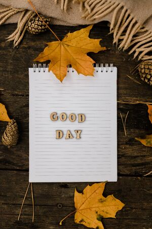 Hands and White blank notebook with wooden letters phrase Good day on a dark background with a scarf, plaid and cup, autumn yellow leaves and pine cones around. View from above. flat lay, in blur. Copy space.