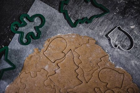 cut out gingerbread cookie in the form of a Christmas tree, star, little man, hearts from raw dough on parchment baking paper on a dark background. Top view. save space. 版權商用圖片