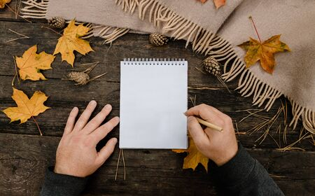 Human hands with a cup of coffee and scarf at wooden table with notebook and pen and autumn leaves. Human hands with a cup of coffee and scarf at wooden table. 版權商用圖片