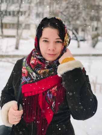 Portrait of a young caucasian happy woman in national russian patterned shawl on a snowy winter day. Stok Fotoğraf