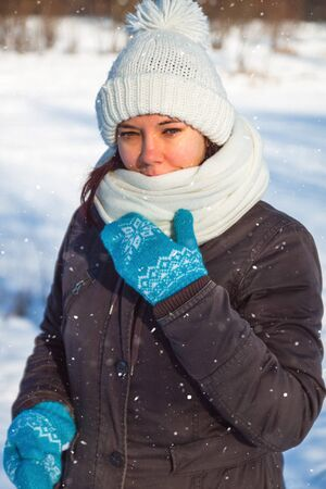 Happy young european woman in white knitted hat and scarf and blue holiday mittens laughing under the snow.