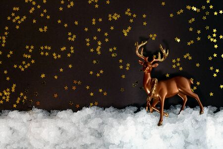 Miniature deer in the snow and dark background with shiny stars with copy space. Christmas composition, postcard template.