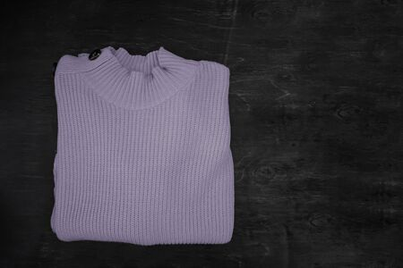 Folded lilac gray knitted sweater on a dark wooden background with copy space. Flat lay Stockfoto