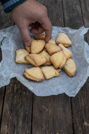 Mans hand takes curd shortbread cookies with triangles on white parchment on an old dark wooden background