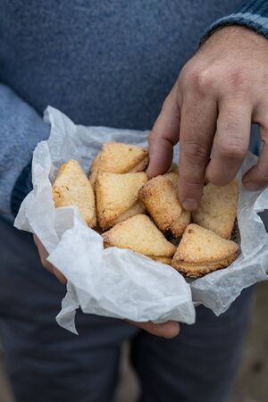Man holds curd shortbread cookies in triangles in white parchment paper