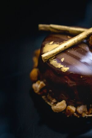 Luxury chocolate cake-cake decorated with a golden decor of caramelized popcorn on a dark background. Flat lay. Close-up. Copy space.