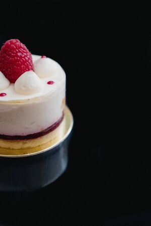 Luxury white cheesecake mousse cake decorated with fresh raspberries on a dark background. Flat lay. Close-up. Copy space