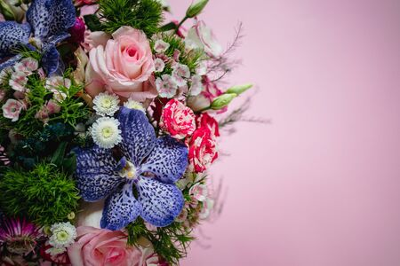 stylish trendy delicate bouquet with a variety of spring flowers, roses, orchids in a round box on a pink background. Copy space.
